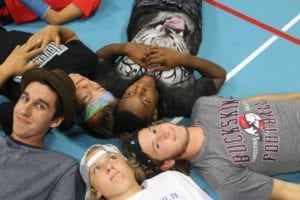 Counselors and campers take a break between games in the gymnasium